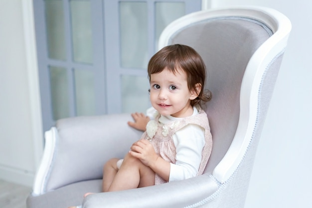 Sweet little girl in pastel pink dress at home sitting on modern cozy grey chair