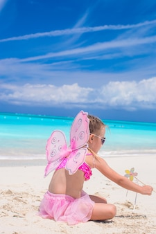 Sweet little girl with butterfly wings on white beach