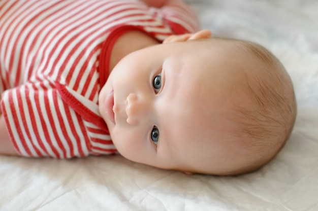 Sweet little newborn baby laying in a bed