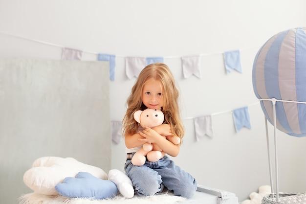 Милая маленькая рыжая девочка обнимает плюшевого мишку дома.