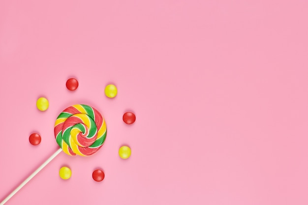 Sweet lollipop and candy on pink background, copy space. love to colorful sweetmeats in childhood concept