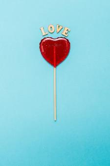 Сладкий леденец на палочке на синем фоне. красное сердце. конфеты. концепция любви. день святого валентина