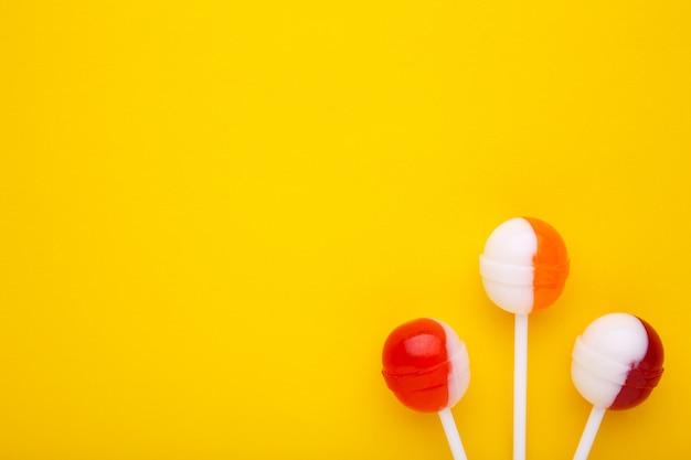 Сладкие леденцы на палочке на желтом фоне. концепция сладких конфет