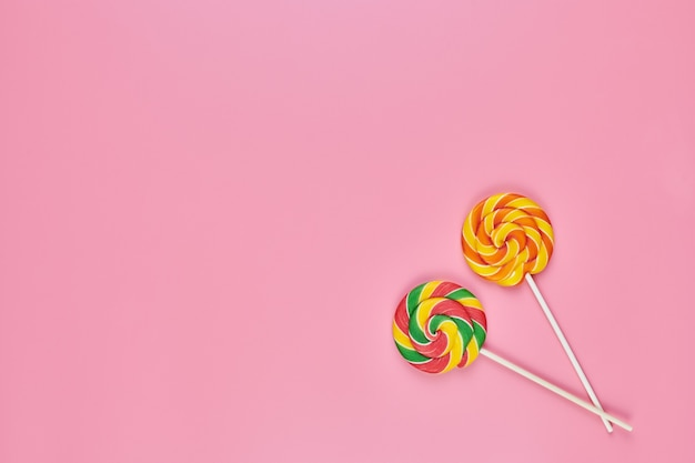 Sweet lollipops on pink background, copy space. love to colorful sweetmeats in childhood concept
