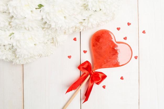 흰 꽃과 활과 막대기에 달콤한 롤리 하트