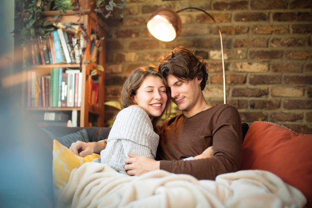 Sweet loving couple spending time at home, cuddling on the sofa - young people living in a cozy and stylish apartment with brick walls