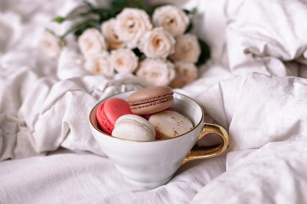 Sweet macaroons in mug and white roses