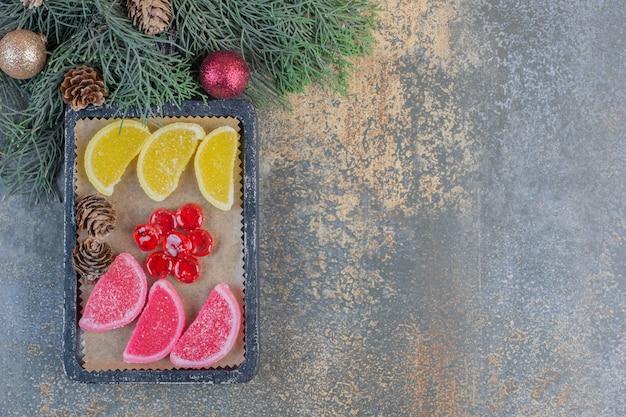 Сладкий мармелад в темных тарелках с рождественскими шишками. фото высокого качества
