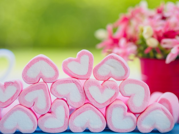 Sweet marshmallow in the shape of heart on wooden plate and flower at background