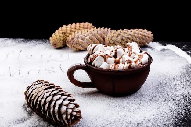 黒い背景に茶色のカップにチョコレートと甘いマシュマロ