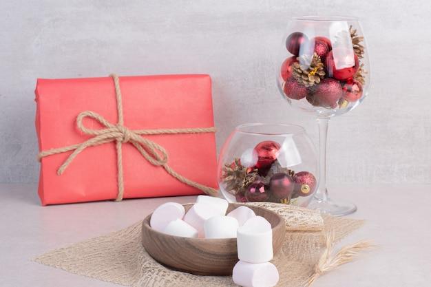 Сладкие зефиры на деревянной тарелке с бокалом красных новогодних шаров