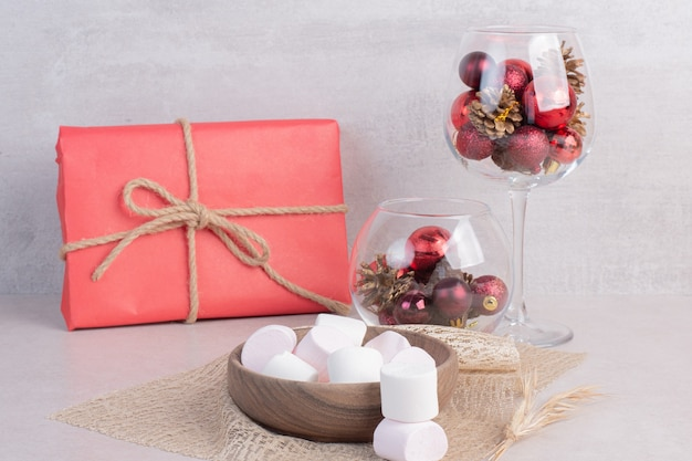Marshmallow dolci sul piatto di legno con un bicchiere di palline rosse di natale