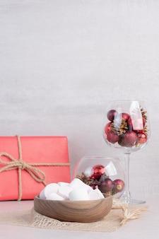 Marshmallow dolci su un piatto di legno con un bicchiere di palline rosse di natale