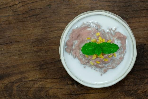 나무 배경에 흰색 그릇에 코코넛 밀크와 달콤한 매쉬 타로