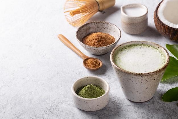 白い背景のコピースペースにココナッツミルクと甘い抹茶ラテ日本茶。
