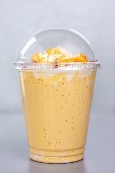 Сладкий молочный коктейль с попкорном в пластиковом стакане.