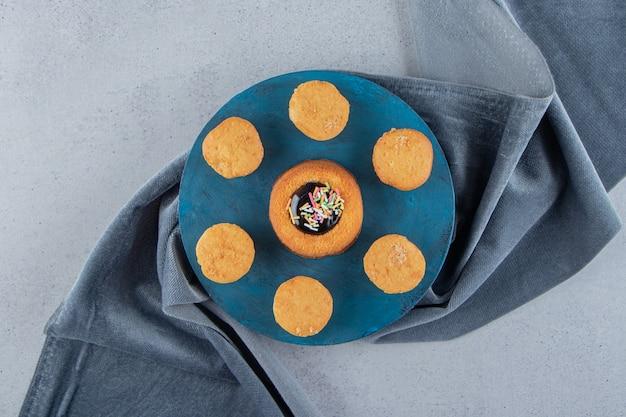 青いボードにゼリーとビスケットが入った甘いミニケーキ。高品質の写真