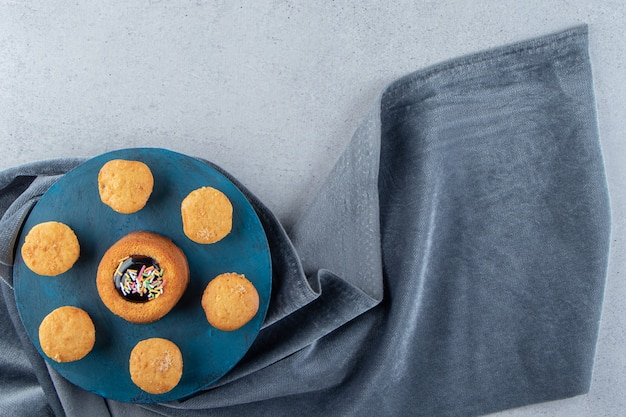 Mini torta dolce con gelatina e biscotti su tavola blu