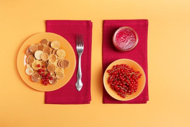 オレンジ色のプレートの甘いミニパンケーキは赤いナプキンの上に立っています