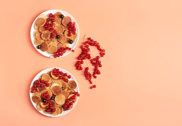 桃の白いプレートに赤と黒のスグリの甘いミニパンケーキ