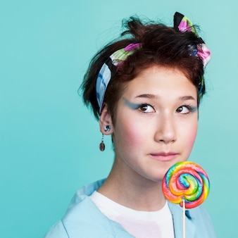 Sweet model posing with multicolored lollipop