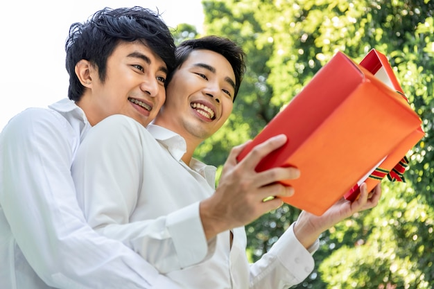Sweet moment of love.portrait of asian homosexual couple hug and surprise box gift to boyfriend