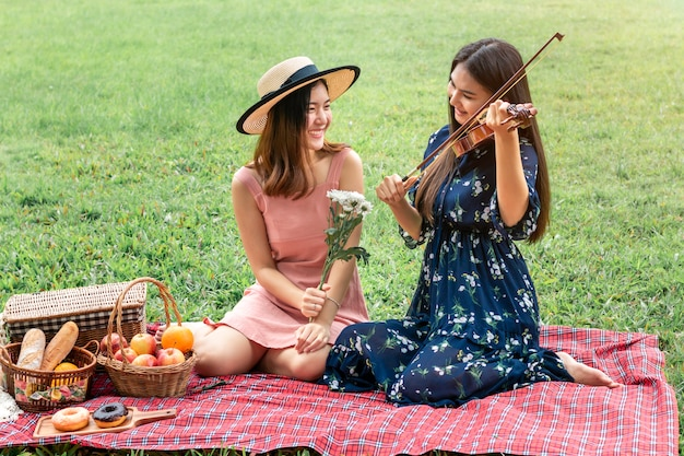 Sweet moment of love.portrait of asian homosexual couple playing with violin and picnic in the park.concept lgbt leasbian.