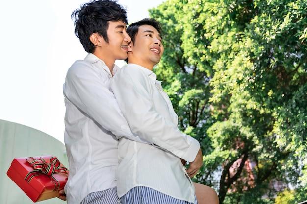 Сладкий момент любви. портрет азиатской гомосексуальной пары обнимает и преподносит сюрприз подарочной коробке парню. концепция лгбт-гея.