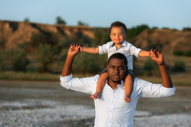 Sweet moments of fatherhood concept. excited african american man giving piggyback ride to happy