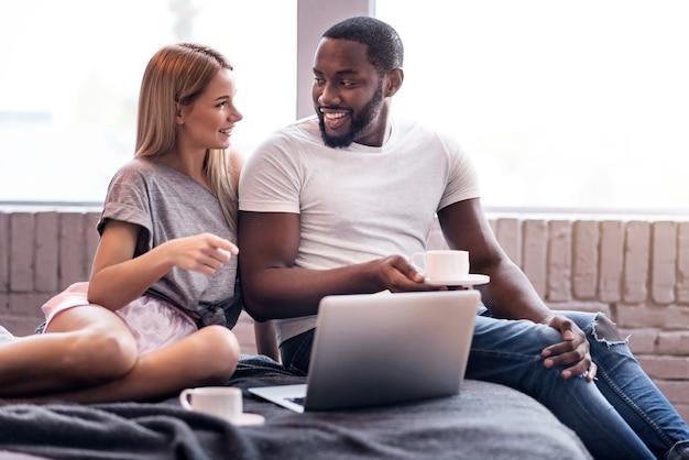 Сладкое утро. обрадованная молодая пара из разных стран пьет чай в постели, используя ноутбук и общаясь.