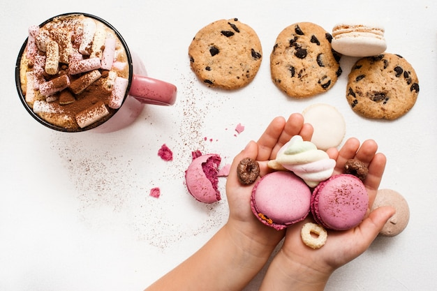 Сладкое утро с горячим какао и любимым печеньем. неузнаваемый ребенок с разноцветными миндальным печеньем в ладонях, шоколадной лепешкой и вкусным напитком с зефиром на белом столе рядом, вид сверху