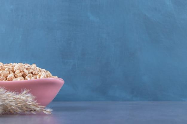 青い背景に、パンパスグラスの横にあるボウルに甘いミューズリー。