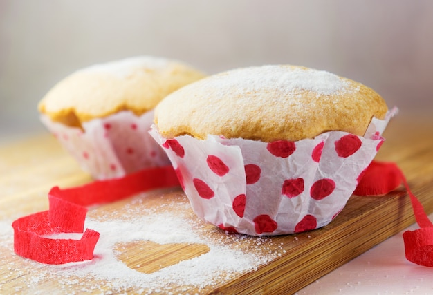 Sweet muffin with sugar and red ribbon decoration