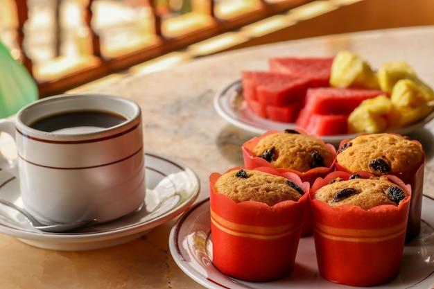 甘いマフィン、コーヒー、フルーツ-インドネシアのバリ島にあるホテルでの伝統的な朝食、天蓋の下の通りにあるレストラン