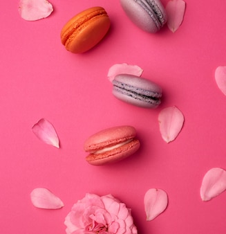 Сладкие разноцветные макаруны со сливками и розовым бутоном розы с разбросанными лепестками