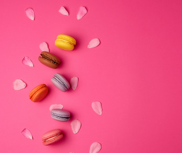 Sweet multi-colored macarons with cream and a pink rose petals