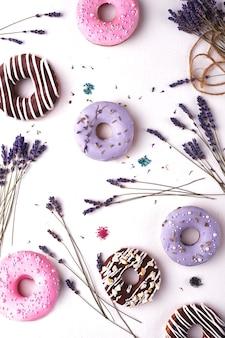 Сладкие разноцветные пончики на белом фоне с цветами лаванды.