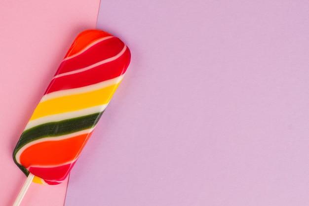 カラフルな紙に甘い色とりどりのロリポップ。ピンクの紙にスティックにカラフルなキャンディー。上面図