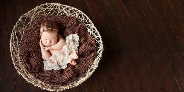 甘い生まれたばかりの赤ちゃんの女の子がバスケットで眠ります。ダークブラウンの背景。コピースペース
