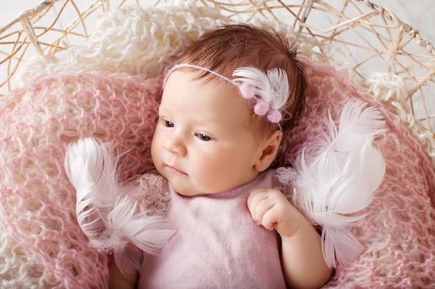 目を開けて甘い新生児の女の子。ニットの格子縞のバスケットに横たわっている3週齢の新生児の女の子。かなり生まれたばかりの女の子の肖像画。クローズアップ画像