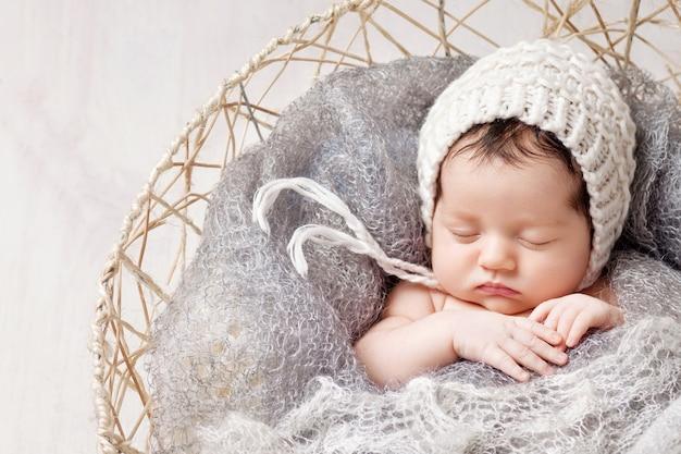 甘い新生児はバスケットで眠ります。クマのおもちゃで美しい新生児。
