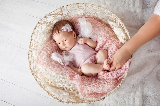 Sweet newborn baby sleeps with a toy in the basket.
