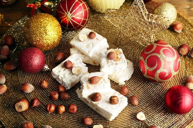 ヘーゼルナッツとクリスマスの装飾テーブルの甘いヌガーをクローズアップ