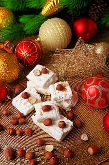헤이즐넛과 크리스마스 장식 테이블과 달콤한 누가를 닫습니다.