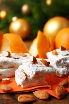 테이블에 오렌지와 크리스마스 장식이 있는 달콤한 누가가 클로즈업