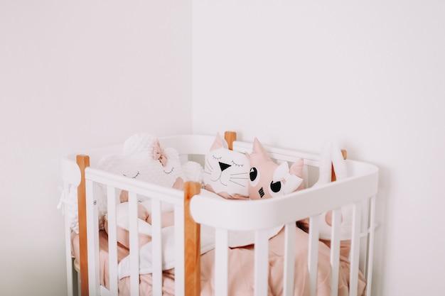 Милые украшения детской комнаты стильный интерьер детской комнаты с удобной кроваткой и забавными розовыми декоративными подушками