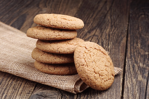 나무 탁자에 있는 거친 천으로 만든 냅킨에 달콤한 귀리 쿠키