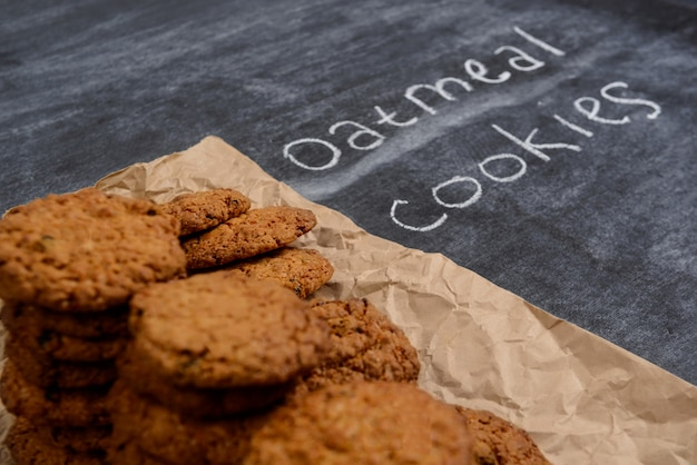 Sweet oatmeal cookies on baking paper at wooden table