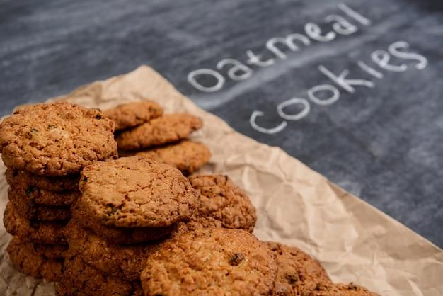 木製のテーブルで紙を焼くの甘いオートミールクッキー