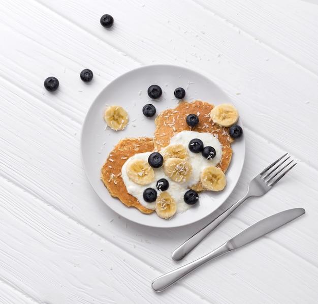 Сладкие овсяные блины со сливками, черникой и бананом. концепция здорового завтрака.